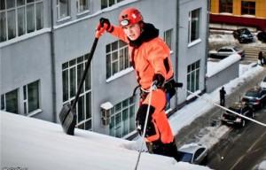 Уборка снега с крыш альпинистами