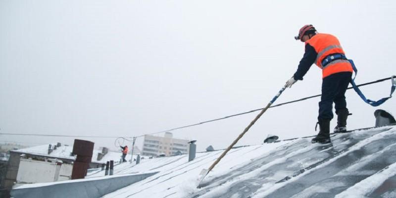 Уборка снега с крыш промышленными альпинистами